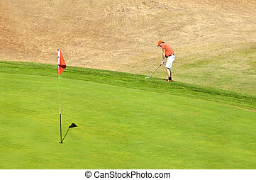 Golf player using a wedge to put his ball on the green near...