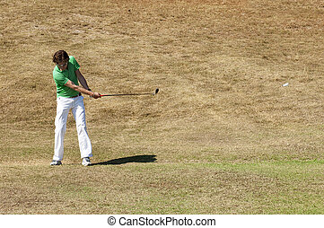 Golf swing - Golf player hitting his ball on the fairway of...