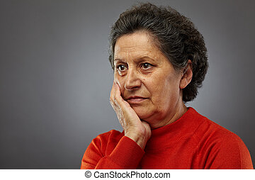 Sad senior woman in thoughts
