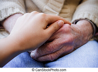 Young holding senior's hands - Young put her hand on senior...