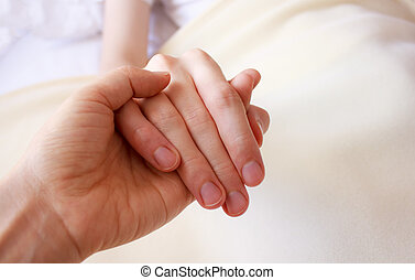 Holding the hand of sick loved one - Holding the hand of a...