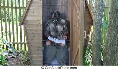 Gas Mask man - Male sitting in a summer toilet with Gas Mask...