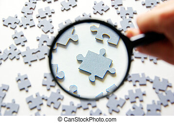 magnifying glass and puzzle - Hand with magnifying glass and...