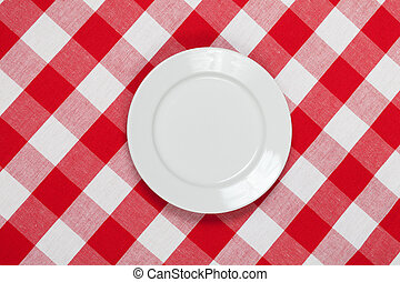 white round plate on red checked tablecloth