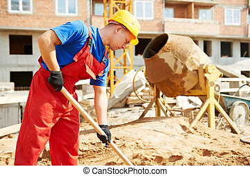 builder worker at construction site with shovel - builder...