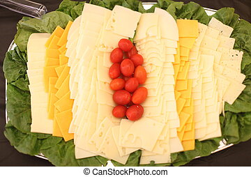 Gourmet cheese tray with tomatoes.