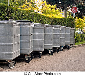 Metal garbage bins on a street lined an a row