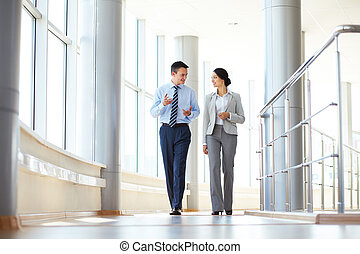 Talking colleagues - Confident business partners walking...