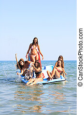 six beautiful young women on a pedalo boat - Group of six...