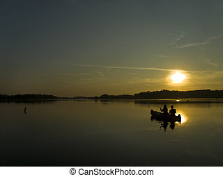 canooing trip into dawn - two persons sitting in a boat and...