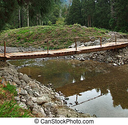 wooden bridge and stream - wooden bridge crossing a small...