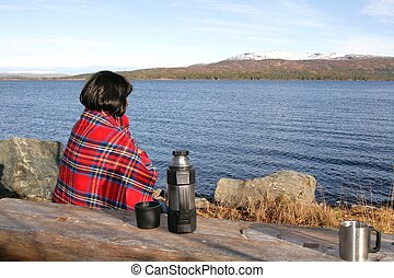 Lonely woman wrapped in a red plaid sitting by a lake with...
