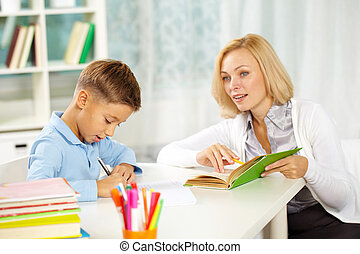 Dictation - Portrait of diligent boy writing dictation with...