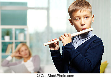 Young flute player - Portrait of cute boy playing the flute...