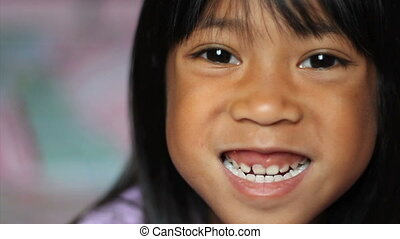Girl Wiggling Her Loose Front Tooth - A cute little 5 year...