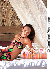 Beautiful girl relaxing outdoor at summer lounge beach club...