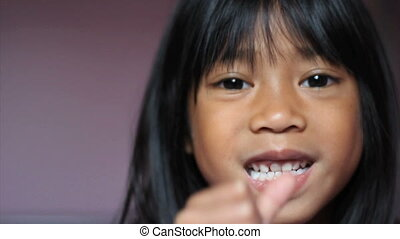 Girl Wiggling Her Tooth-Close Up - A cute little 5 year old...