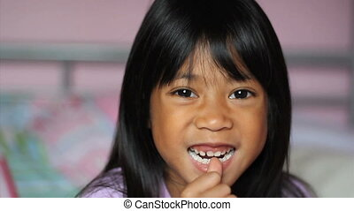 Girl Wiggling Her First Loose Tooth - A cute little 5 year...