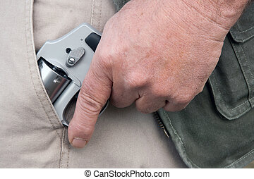 concealed carry - man drawing a concealed weapon from his...