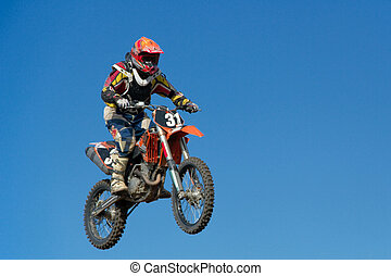 Motorcycle jumping against blue sky