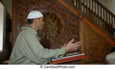 Imam preaching in a mosque - Imam, islamic priest praying in...