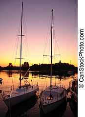 Yachts at colorful sunset background