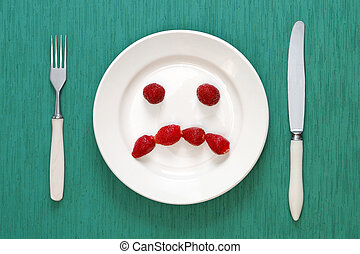Fork, knife and sad face made of strawberries on plate