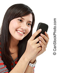 Beautiful young Asian woman smiles while writing a text...