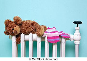 Teddy bear and gloves on an old radiator