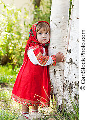 little girl in Russian traditional dress standing next to a...