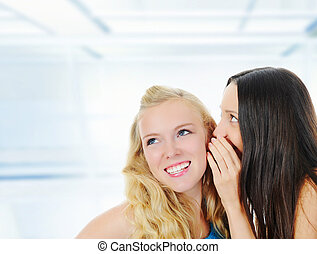 Two beautiful women telling secret - image of a two...