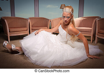 Young bride in white dress seated on the floor.