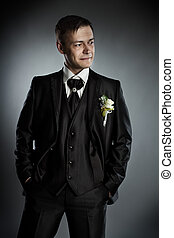 Handsome man in black suit. Grey background. - Handsome man...