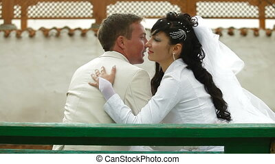 Bride and groom on bench in park - Crimean Tatar newlyweds...