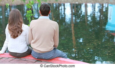 Couple in park - Young couple sitting in park at water