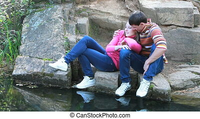 Ideal love - Young couple kissing on rocks by water