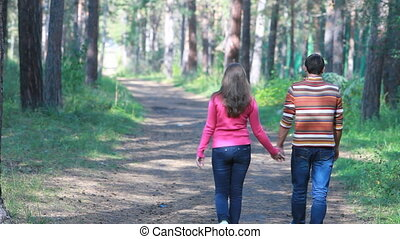 Couple in wood - Rear view of couple walking in forest...