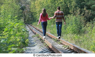 Walk on rails - Young couple walking on rails in wood