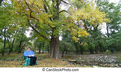 golden autumn - elderly woman sitting in a chair at autumn...