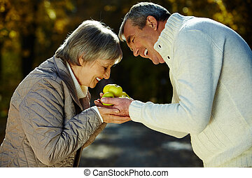 Smell of apples - Photo of aged woman smelling apples in her...