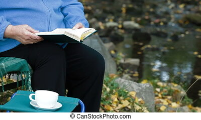 reading book with cup of coffee - Elderly woman reading a...