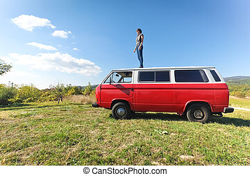 Road trip - Young woman on the roof of her red van on road...
