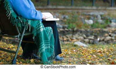 Senior woman enjoying Retirement with a book at autumn park...