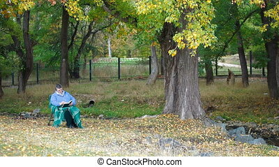 Senior woman sitting outdoors in chair under autumn tree,...