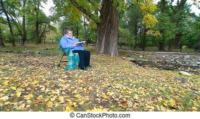 Senior Woman Reading Book in Autumn