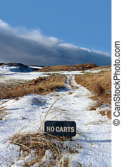 no carts sign on a snow covered links golf course in ireland...