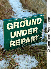 ground under repair sign on snow covered links golf course
