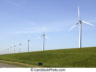 Windturbines on a dike in the Nertherlands near a motorway