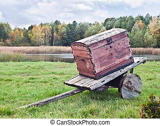 Old wagon with a chest against the autumn landscape