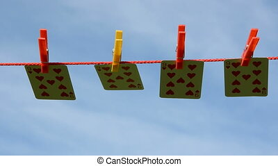 four playing cards on clothes-line and summer wind